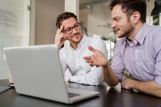 Businessman with male colleague discussing over laptop in office