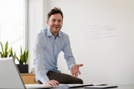Smiling businessman with document at desk in office