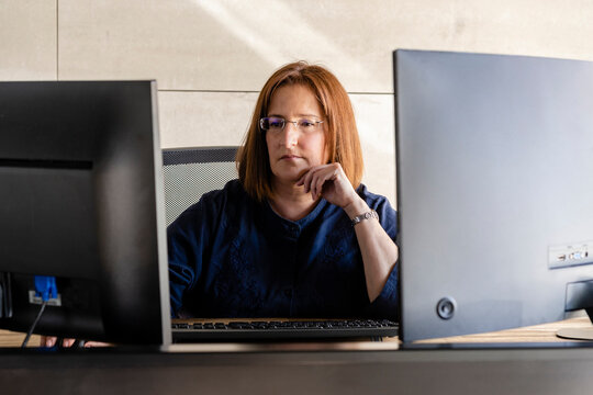 Mature businesswoman in eyeglasses working on computer while sitting at desk in office