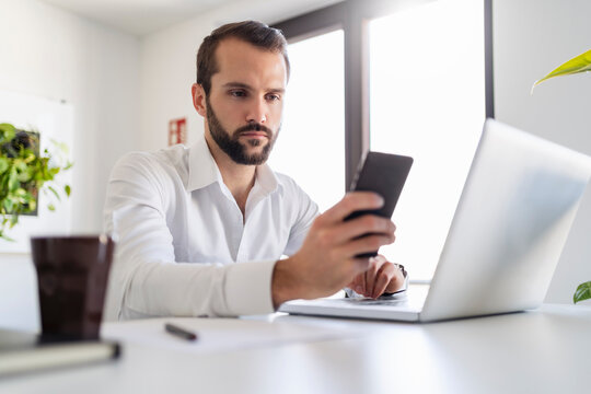 Young entrepreneur with laptop using mobile phone while sitting at office