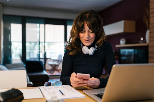 Woman with laptop smiling while using mobile phone at home