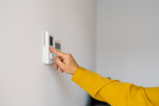 Mature woman adjusting thermostat at home