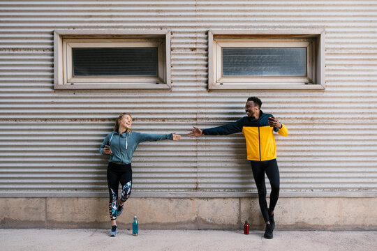 Smiling male and female athlete holding mobile phone while shaking hands against wall