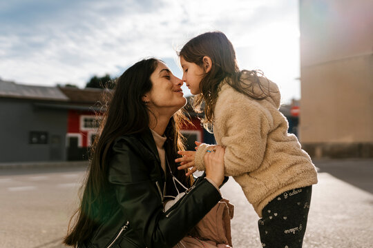 Daughter rubbing nose with mother while standing on road
