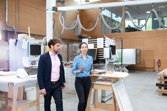 Male and female entrepreneurs discussing while walking in factory