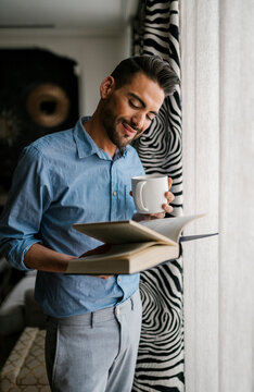 Man with coffee cup reading book while standing at home