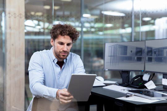 Young businessman using digital tablet while sitting at desk in office