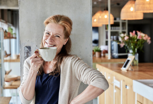 Happy mature woman with hand on hip having coffee against column at home