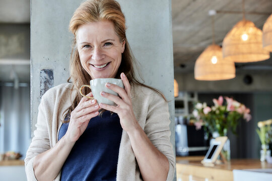 Smiling mature woman holding coffee cup against column at home