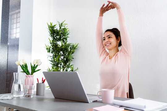 Young woman with hand raised using laptop while sitting at home office