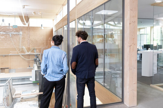Businessman and businesswoman looking through glass wall in factory