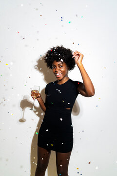 Confetti falling on happy woman dancing with champagne flute while standing against white background