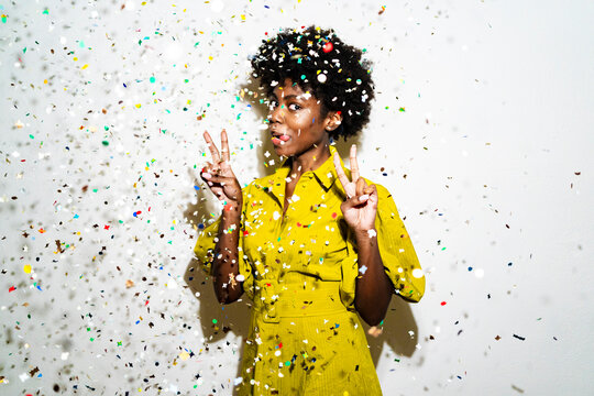 Woman showing peace sign and sticking out tongue while standing amidst confetti against white background