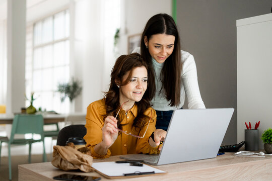 Smiling daughter with mother looking at laptop while sitting at desk in home office