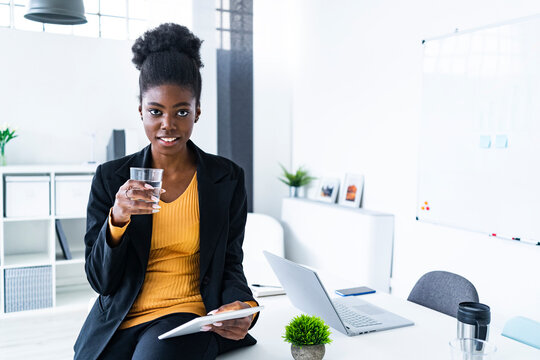 Young female Afro entrepreneur holding glass of water and digital tablet in office