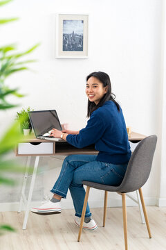 Young woman sitting with laptop by table at home office