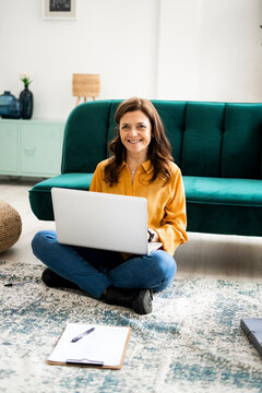 Smiling woman with laptop sitting on floor at sofa in living room