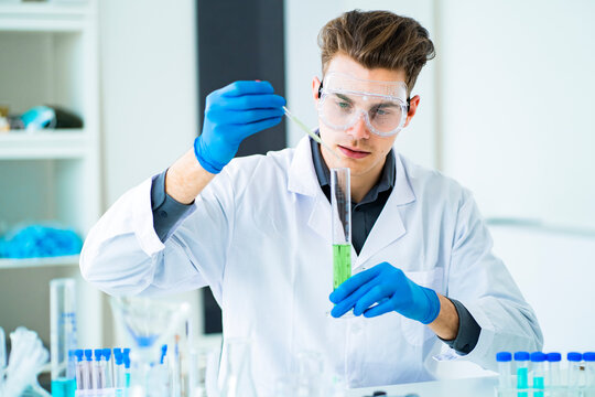 Young scientist mixing chemicals in graduated cylinder at laboratory