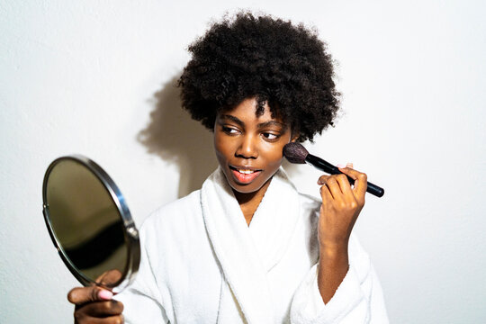 Curly hair woman in bathrobe doing make-up while standing against white background