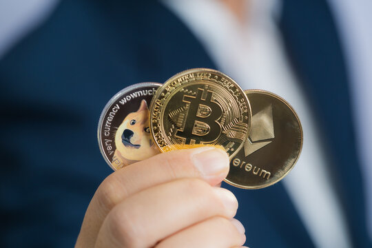 Golden bitcoin coin Dogecoin DOGE, Ethereum ETH group included with Cryptocurrency on hand business man wearing a blue suit. Filed and put and give to me on 04 29 2021
