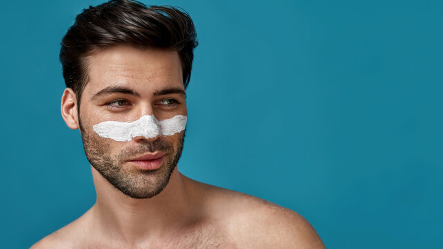 Portrait of playful brunette man with white mask applied on nose for cleansing pores posing isolated over blue background