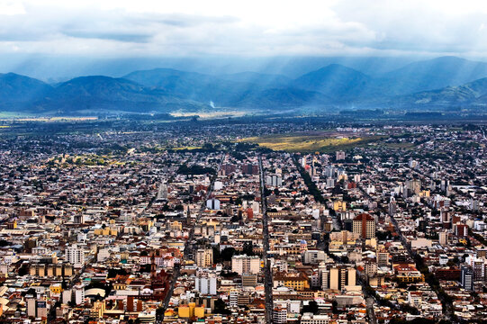 Looking down to the city sprawl of Salta in northern Argentina with storm clouds over the Andes.