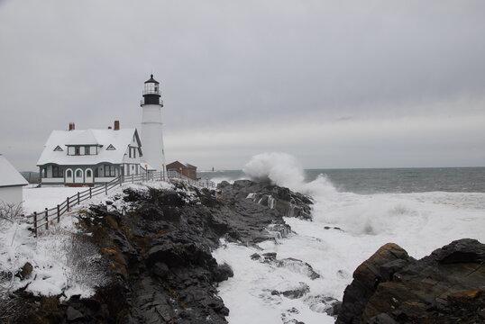 A winter ocean storm pounds huge surf on the rocks at Portland Headlight, Cape Elizabeth, Maine