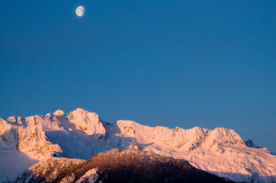 Sunrise over mountains near Squamish, Canada with the moon still up.