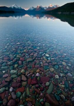 Clear water of Lake McDonald shows colorful rocks on lake bottom, Glacier National Park, Montana