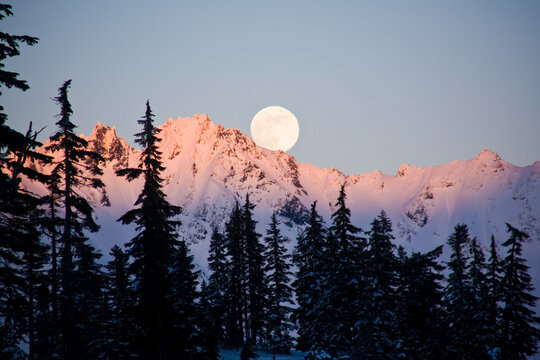 Moonrise over the North Cascades at sunset, as seen from Mount Baker, Washington.