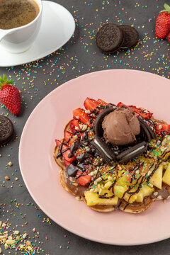 Heart waffle with pineapple and strawberry with gummy candy and ice cream on it.
