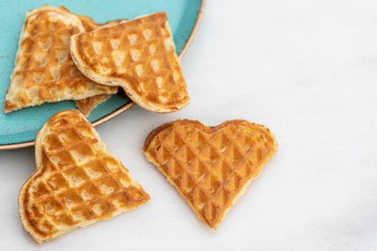 Heart shaped waffles standing scattered in green plate on white marble table
