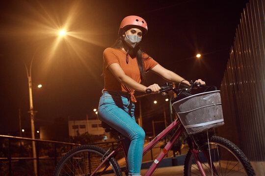 hermosa Mujer joven maneja feliz en bicicleta por un parque por la ciudad. Modelo ciclista en mascarilla