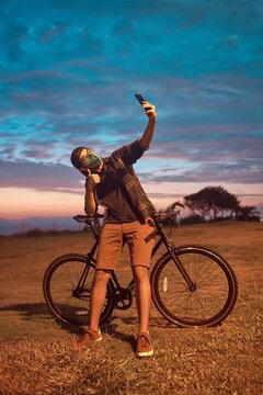 atractivo hombre joven maneja feliz en bicicleta por un parque por la ciudad. Modelo ciclista en mascarilla