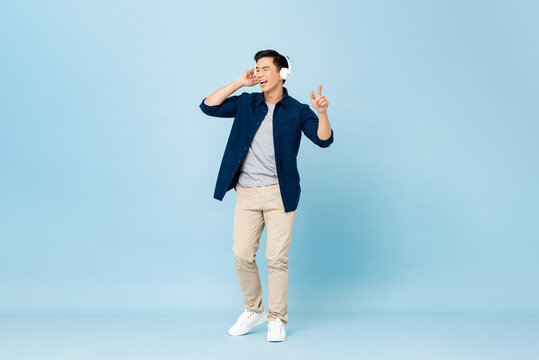 Smiling enjoyful young handsome Asian man listening to streaming music on wireless headphones isolated on light blue studio portrait background