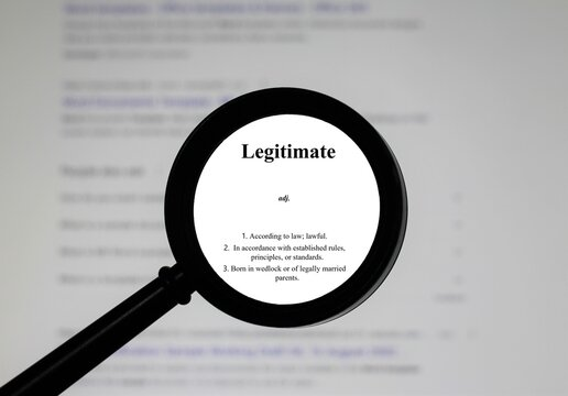 Selective focus on word legitimate, word in a dictionary. Close up of an English dictionary page with the word legitimate