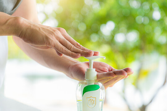 Taking disinfection alcohol gel on hands in the park.