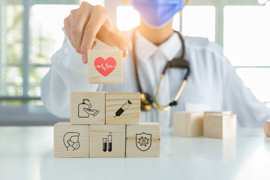 Doctor hand choosing medical symbol HEART on cube wooden toy blocks.