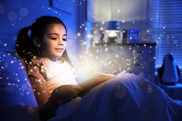 Little girl reading fairy tale in dark bedroom