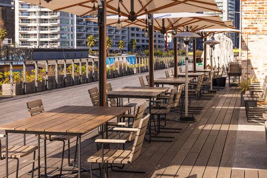 レストランの前の木製テラスにある日除けパラソルとテーブル