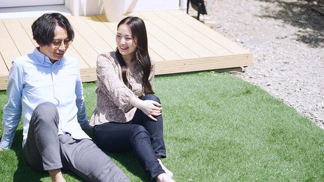 芝生でリラックスする爽やかなカップル