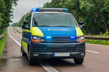 Fototapeta Police car from Germany from the state of Brandenburg on the autobahn. Switched on blue light and warning lights on the vehicle. Two-lane carriageway in wet weather