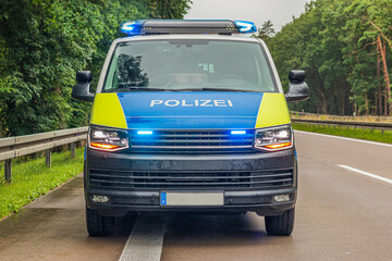 Fototapeta Front view of a police car on the highway. Switched on blue light in the headlights of the police car. Rainy weather in spring with green trees. Concrete asphalt with two lanes and hard shoulder