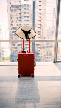 Verticle view  and  Selective focus of Red luggage with white hat  for a travel lifestyle in a city as building background, Travel holiday concept