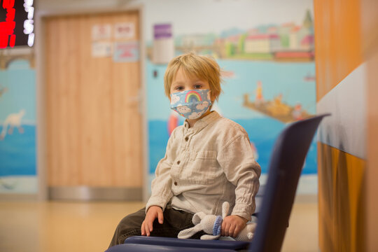 Child, boy, sitting in the waiting room in emergency, waiting for examination