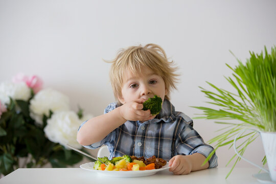 Little toddler child, blond boy, eating boiled vegetables, broccoli, potatoes and carrots with fried chicken meat at home