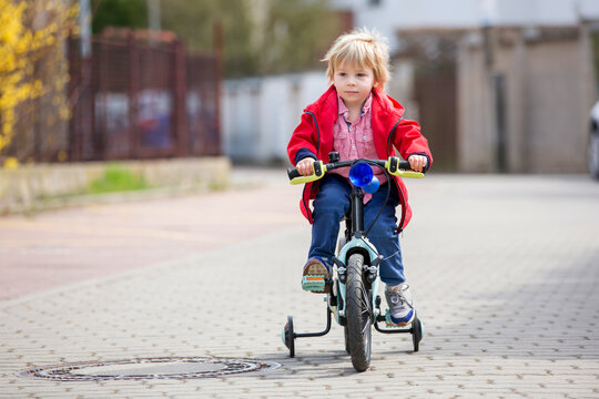 Little boy, learning how to ride a bike in the parkLittle child, blond boy, learning how to ride a bicycle in the park using helping wheels on the side