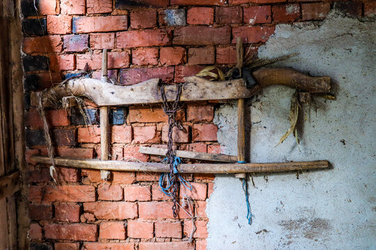 A very old wooden yoke for cattle hanging on a rustic wall in a stall on country