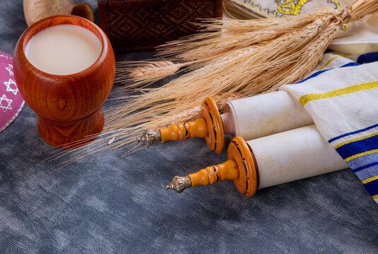 Torah and tallis in the Traditional celebration season Jewish holiday Shavuot on kosher dairy food