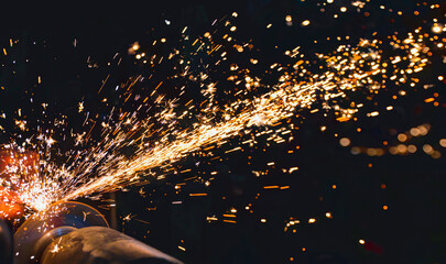 Hot sparks at grinding steel material  - fototapety na wymiar